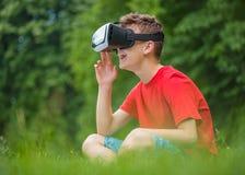 Muchacho adolescente con los vidrios de VR en parque Foto de archivo