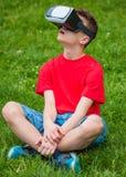 Muchacho adolescente con los vidrios de VR en parque Imagen de archivo libre de regalías