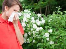 Muchacho adolescente con rinitis alérgica en un jardín de la primavera Imagenes de archivo