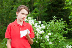 Muchacho adolescente con rinitis alérgica en un jardín de la primavera Fotografía de archivo