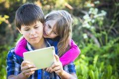 Muchacho adolescente con su hermana más joven que se sienta en un parque Fotografía de archivo libre de regalías