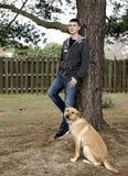 Muchacho adolescente con su perro al aire libre Imagen de archivo libre de regalías