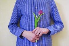 Muchacho adolescente con un tulipán violeta en manos Fotos de archivo libres de regalías