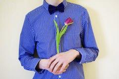 Muchacho adolescente con un tulipán violeta en manos Imagenes de archivo
