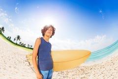 Muchacho adolescente confiado listo para practicar surf Imagen de archivo libre de regalías