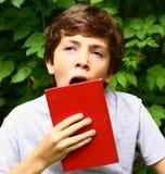 Muchacho adolescente de bostezo con el libro Imagen de archivo