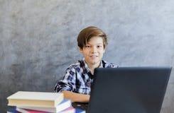 Muchacho adolescente de la edad que trabaja en el ordenador portátil Fotos de archivo libres de regalías