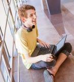 Muchacho adolescente de la expresión positiva con el ordenador portátil y el auricular Imagen de archivo