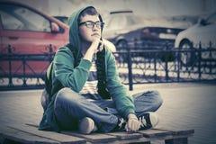 Muchacho adolescente de la moda que se sienta en la acera de la ciudad Fotografía de archivo libre de regalías