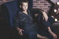 Muchacho adolescente de moda hermoso que se sienta en una silla en casa Imagen de archivo