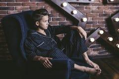 Muchacho adolescente de moda hermoso que se sienta en una silla en casa Fotografía de archivo