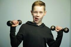 Muchacho adolescente del deporte con las pesas de gimnasia y el corte de pelo elegante, tiro del estudio Foto de archivo libre de regalías