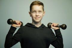 Muchacho adolescente del deporte con las pesas de gimnasia y el corte de pelo elegante, tiro del estudio Fotografía de archivo libre de regalías