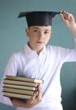 Muchacho adolescente del estudiante en casquillo de la graduación con la pila de los libros Fotos de archivo