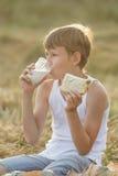 Muchacho adolescente del granjero que goza de la leche y del pan frescos Fotografía de archivo