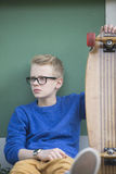 Muchacho adolescente del monopatín del retrato con los vidrios Fotografía de archivo