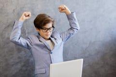 Muchacho adolescente del negocio feliz con el ordenador portátil Fotos de archivo