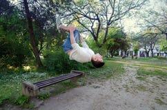 Muchacho adolescente del parkour de la aptitud que hace salto al revés de banco Imagen de archivo