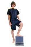 Muchacho adolescente descalzo que se coloca con el ordenador portátil sobre blanco Fotos de archivo libres de regalías