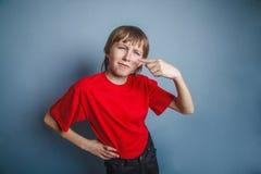Muchacho, adolescente, doce años en la camisa roja, nariz Imagen de archivo
