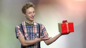 Muchacho adolescente elegante que presenta la caja de regalo almacen de metraje de vídeo