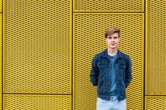 Muchacho adolescente elegante sobre copyspace amarillo industrial del fondo Imagen de archivo libre de regalías