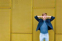 Muchacho adolescente elegante sobre el fondo amarillo industrial que se relaja Foto de archivo libre de regalías