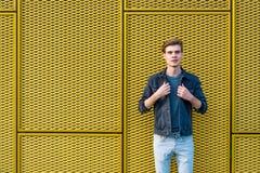Muchacho adolescente elegante sobre fondo amarillo industrial Fotografía de archivo