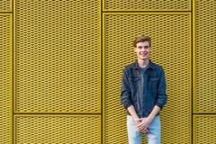 Muchacho adolescente elegante sobre la sonrisa amarilla industrial del fondo Foto de archivo
