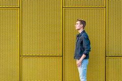 Muchacho adolescente elegante sobre vista lateral del fondo amarillo industrial Foto de archivo