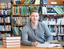 Muchacho adolescente en biblioteca de universidad Imagen de archivo libre de regalías