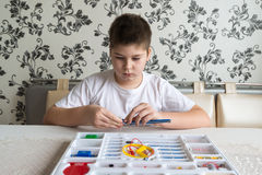 Muchacho adolescente en casa con proyecto electrónico Imagen de archivo