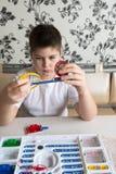 Muchacho adolescente en casa con proyecto electrónico Imagenes de archivo