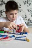 Muchacho adolescente en casa con proyecto electrónico Fotos de archivo