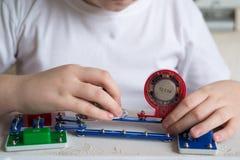 Muchacho adolescente en casa con proyecto electrónico Fotografía de archivo libre de regalías