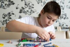 Muchacho adolescente en casa con proyecto electrónico Imágenes de archivo libres de regalías