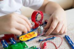 Muchacho adolescente en casa con proyecto electrónico Foto de archivo libre de regalías