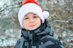 Muchacho adolescente en el casquillo Santa Claus al aire libre Fotos de archivo libres de regalías