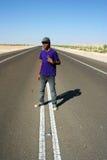 Muchacho adolescente en el centro de la carretera Foto de archivo