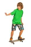 Muchacho adolescente en el monopatín Imagenes de archivo