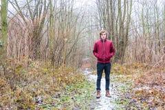 Muchacho adolescente en el parque del invierno que se coloca feliz en nieve Imagenes de archivo