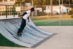 Muchacho adolescente en el parque del patín con un rasgón-palillo Fotos de archivo