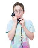 Muchacho adolescente en el teléfono con una expresión fuerte Imagen de archivo