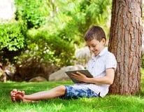 Muchacho adolescente en hierba con la tableta Imágenes de archivo libres de regalías