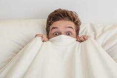 Muchacho adolescente en la cama blanca Fotografía de archivo libre de regalías