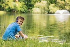 Muchacho adolescente en la orilla del lago Foto de archivo libre de regalías