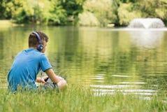 Muchacho adolescente en la orilla del lago Fotos de archivo libres de regalías