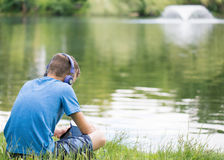 Muchacho adolescente en la orilla del lago Imagenes de archivo