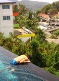 Muchacho adolescente en la piscina del tejado del agua Foto de archivo