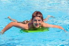 Muchacho adolescente en la piscina que se relaja Imagenes de archivo
